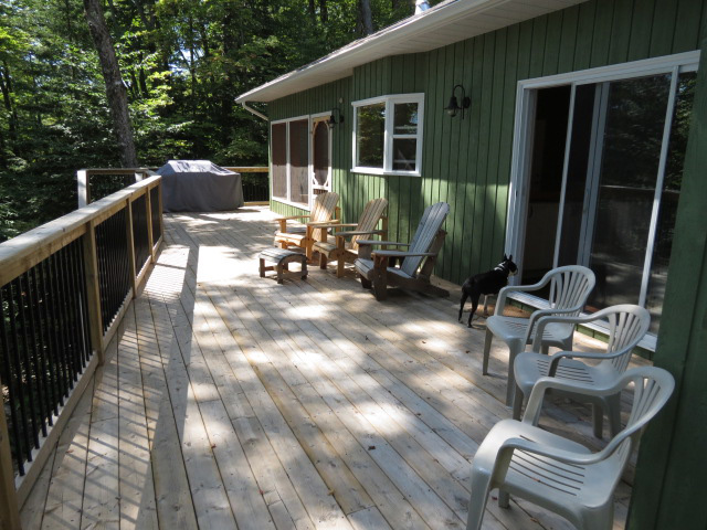 Large deck runs across the front of the cottage with glimpses of the lake through the trees.