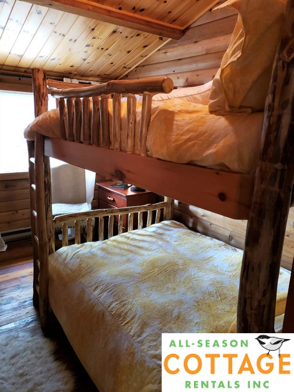 Bedroom #4 is located on main floor with double/double bunks and a view of the lake.