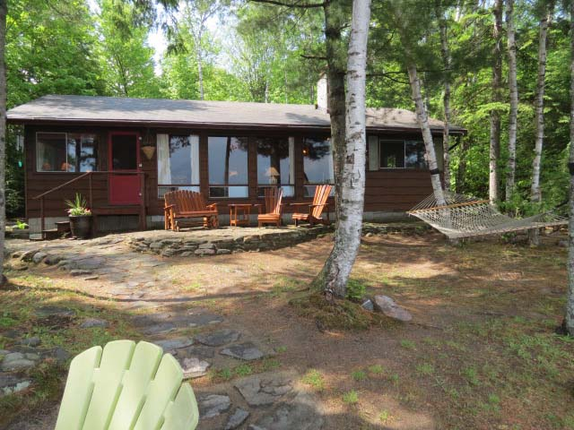 Notice the patio in front of the cottage and a stone path leading to the lake.