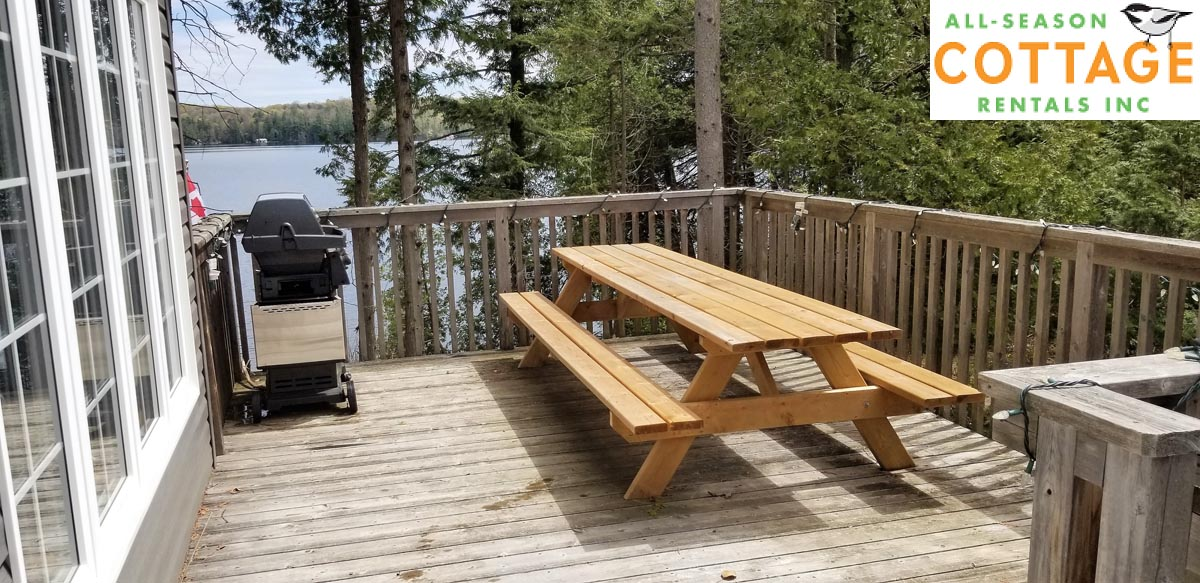Side deck of cottage has a BBQ and large picnic table
