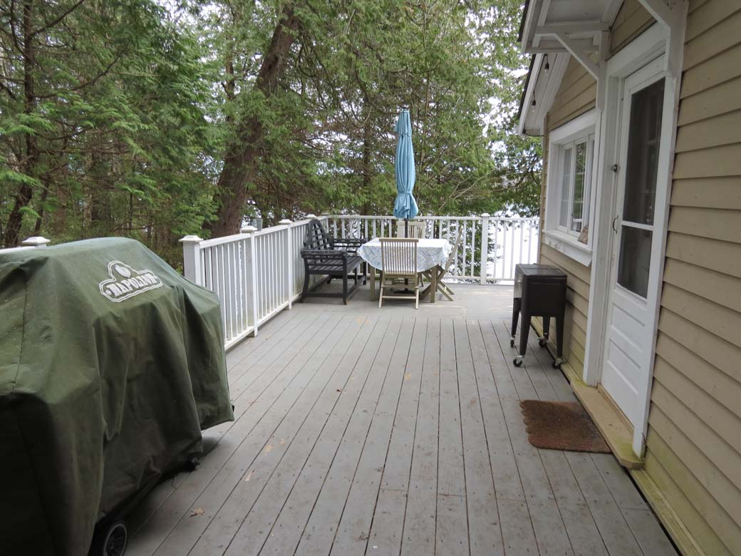 L shaped deck runs along 2 sides of the cottage