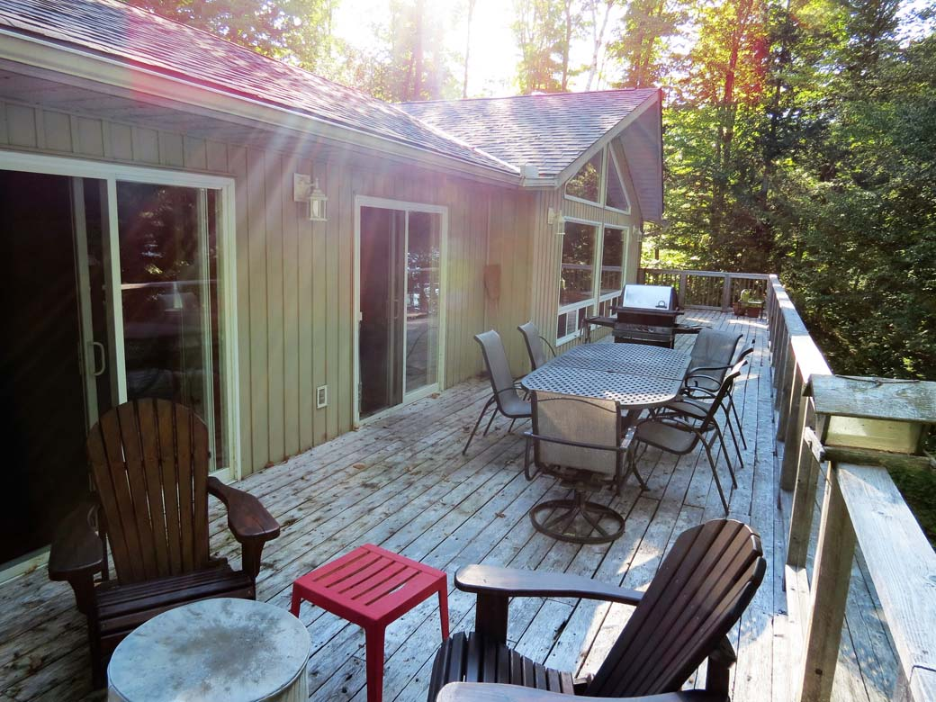 Full length deck runs along  lakeside of cottage with outdoor dining table and lots of seating.
