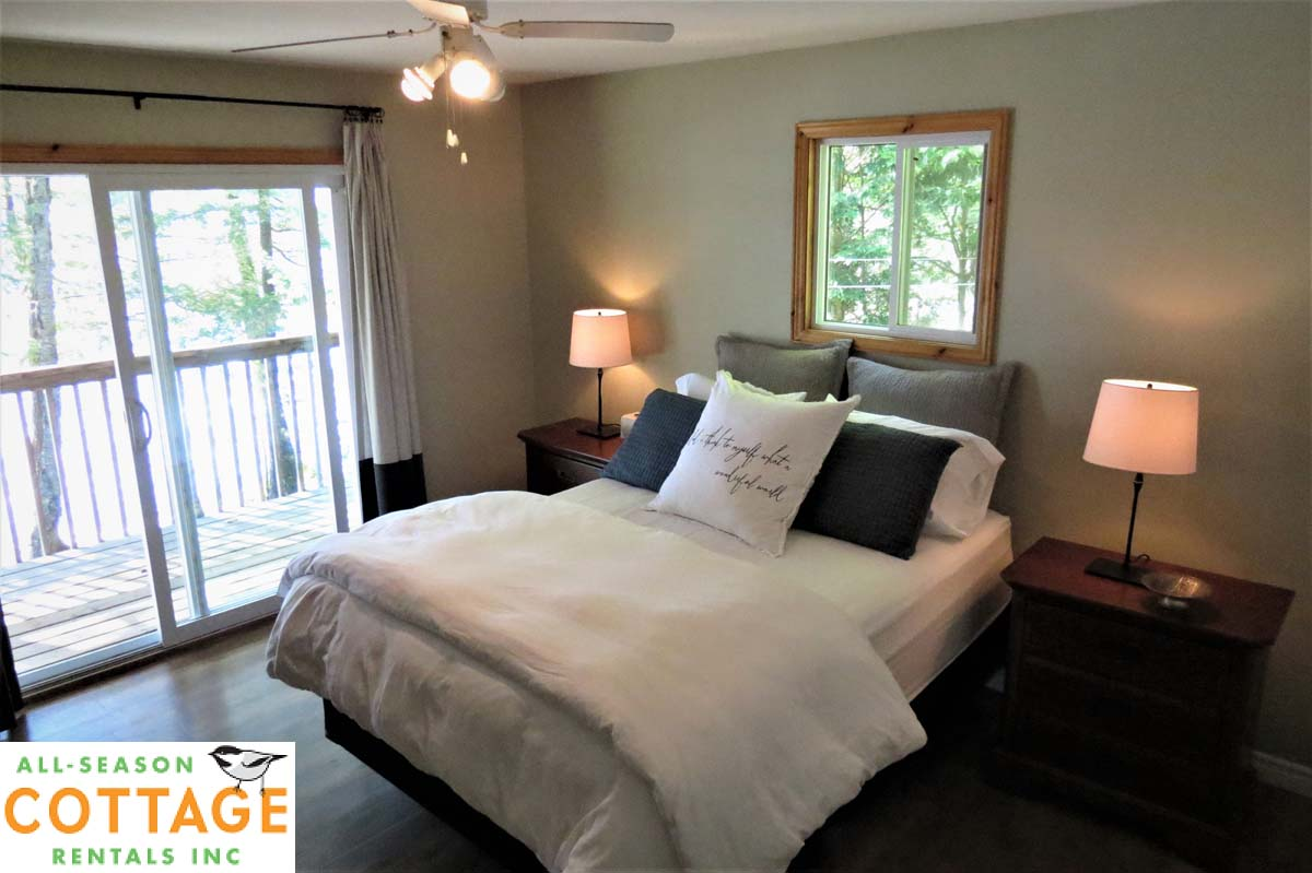 Bedroom #1, on the main floor, has a view of the lake and a walk-out to the deck.