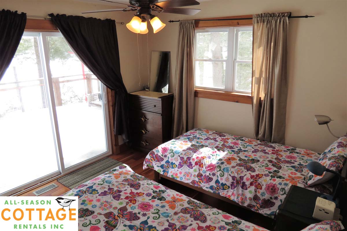 Bedroom #2 is on main floor with two single beds and ceiling fan (plus great view of the lake!)